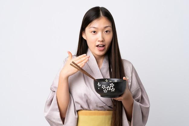 Kimono da portare della giovane ragazza cinese su bianco isolato che tiene una ciotola di tagliatelle con le bacchette e sorpreso