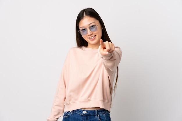 Giovane ragazza cinese over white che punta davanti con felice espressione