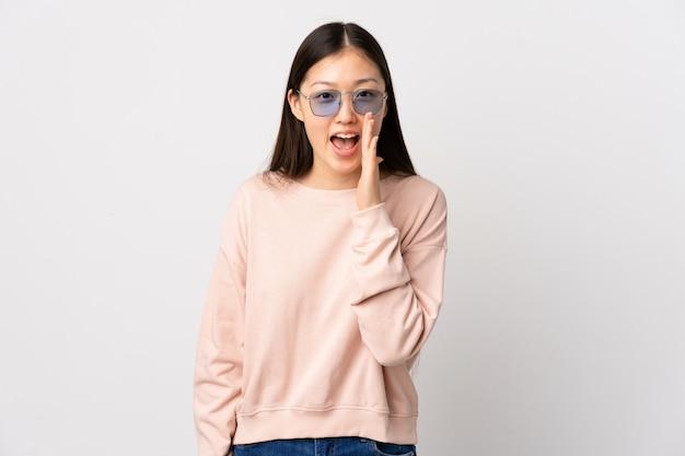Giovane ragazza cinese sopra la parete bianca che grida con la bocca spalancata