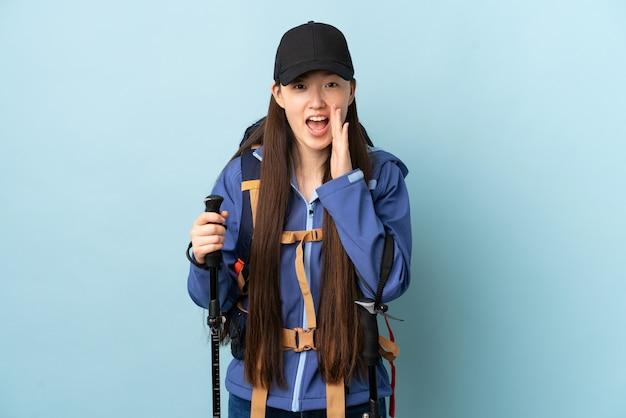 Giovane ragazza cinese con i pali di trekking e dello zaino sopra gridare blu isolato con la bocca spalancata