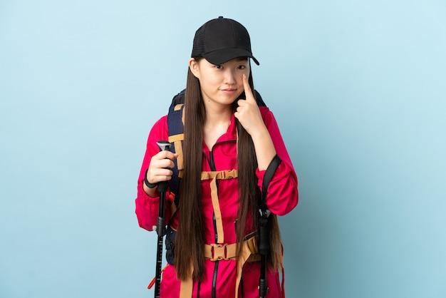 Giovane ragazza cinese con zaino e bastoncini da trekking sopra il blu isolato che mostra qualcosa