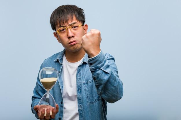 Giovane uomo cinese che tiene un temporizzatore della sabbia che mostra il pugno alla parte anteriore, espressione arrabbiata
