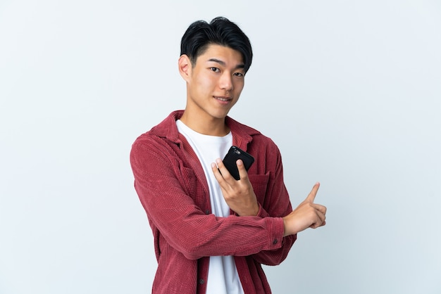 Giovane uomo cinese isolato sul muro bianco utilizzando il telefono cellulare e rivolto indietro