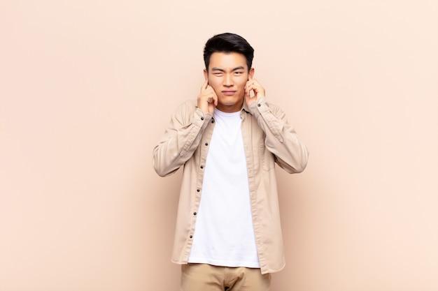 Giovane cinese che sembra arrabbiato, stressato e infastidito, coprendo entrambe le orecchie con un rumore assordante, suono o musica ad alto volume contro una parete a colori piatti