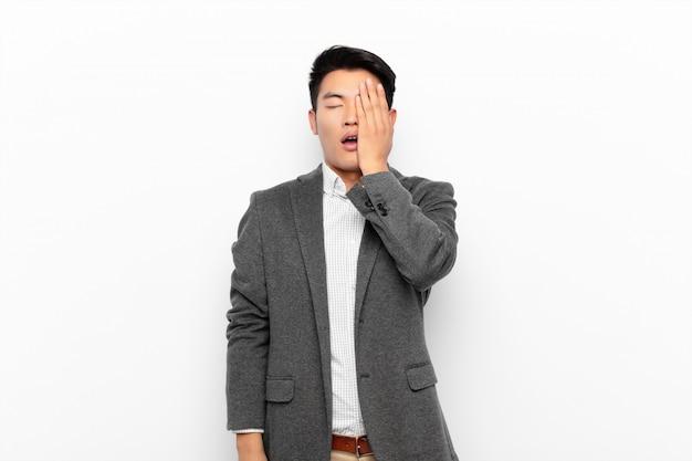 Giovane cinese che sembra assonnato, annoiato e sbadigliando, con un mal di testa e una mano che copre metà del viso contro la parete di colore piatto