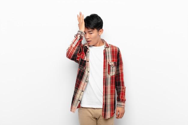 Giovane cinese che solleva il palmo sulla fronte pensando oops, dopo aver fatto uno stupido errore o aver ricordato, sentendosi stupido contro la parete di colore piatto