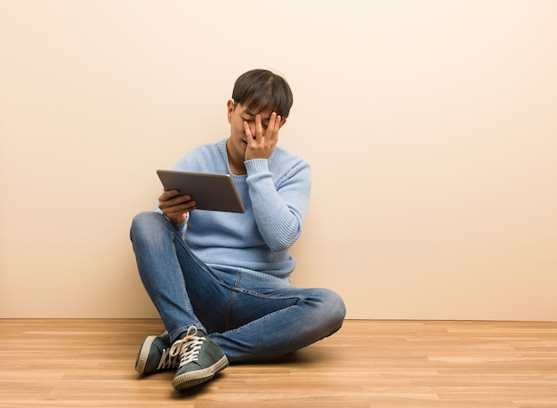 Giovane uomo cinese che si siede usando il suo tablet imbarazzato e ridendo allo stesso tempo
