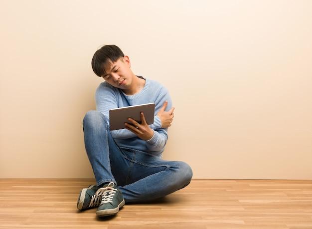 Giovane uomo cinese che si siede facendo uso della sua compressa che dà un abbraccio