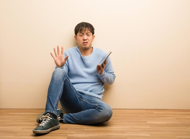 Giovane uomo cinese seduto utilizzando il suo tablet rifiutando qualcosa che fa un gesto di disgusto