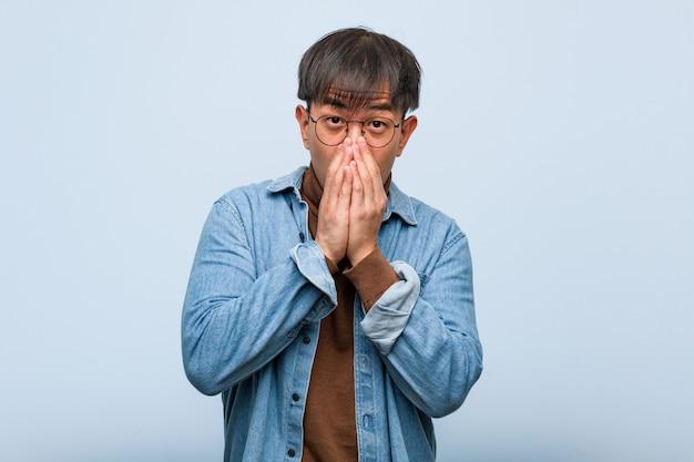 Giovane cinese molto spaventato e impaurito nascosto