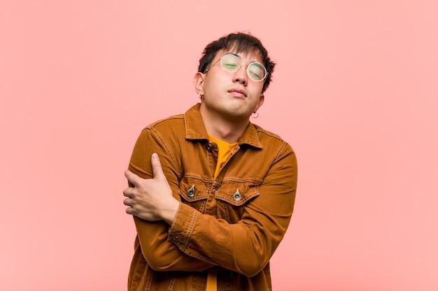 Giovane uomo cinese che indossa una giacca che dà un abbraccio