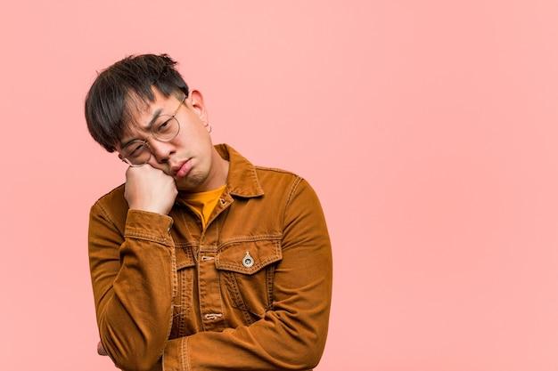Giovane uomo cinese che indossa una giacca pensando a qualcosa, guardando al lato