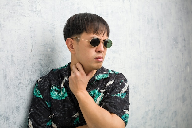 Giovane uomo cinese che indossa abiti estivi tosse, malato a causa di un virus o infezione