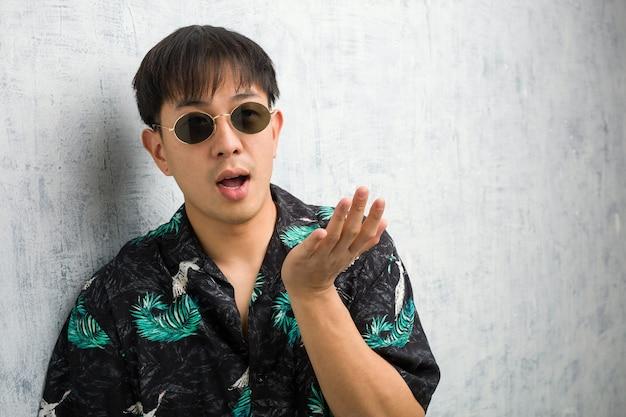 Giovane uomo cinese che indossa un abito estivo tenendo qualcosa con le mani