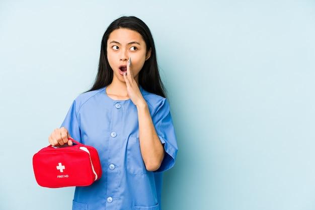 Giovane donna infermiera cinese isolata su uno spazio blu che punta il tempio con il dito, pensando, concentrato su un compito.