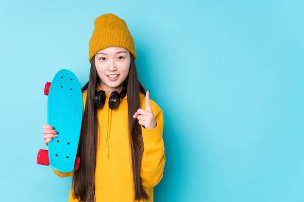 La giovane donna cinese del pattinatore ha isolato il numero di mostra eccessivo con il dito.