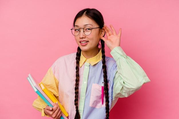 Giovane studentessa cinese in possesso di libri che indossa una camicia multicolore di moda e una treccia, isolata su sfondo rosa cercando di ascoltare un pettegolezzo.