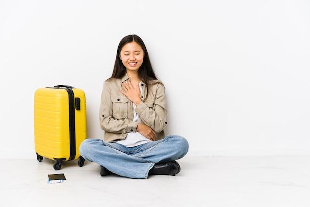La giovane donna cinese del viaggiatore che si siede tenendo i passaggi di un imbarco ride felicemente e si diverte tenendo le mani sullo stomaco.
