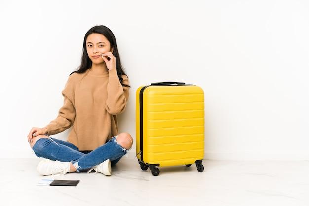Giovane donna cinese del viaggiatore che si siede sul pavimento con una valigia isolata con le dita sulle labbra che mantengono un segreto.