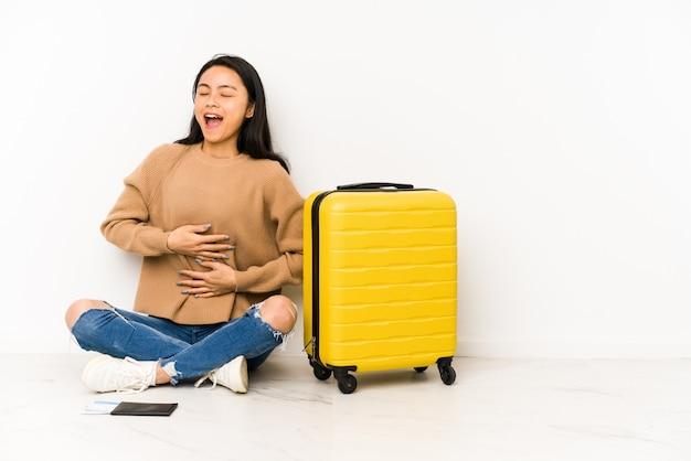 La giovane donna cinese del viaggiatore che si siede sul pavimento con una valigia ride felicemente e si diverte a tenere le mani sullo stomaco.