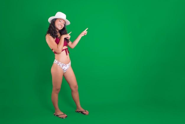 Giovane donna cinese in bikini che indica qualcosa accanto a lei sorridente in chroma key
