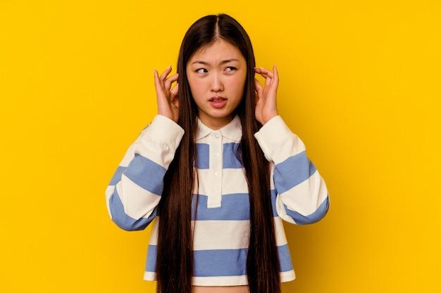 Giovane donna cinese che copre le orecchie con le dita, stressata e disperata da un ambiente rumoroso.