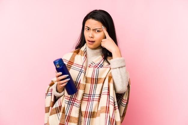 Giovane donna cinese che fa un campeggio isolato su sfondo rosa che punta il dito contro di te come se invitando ad avvicinarsi.