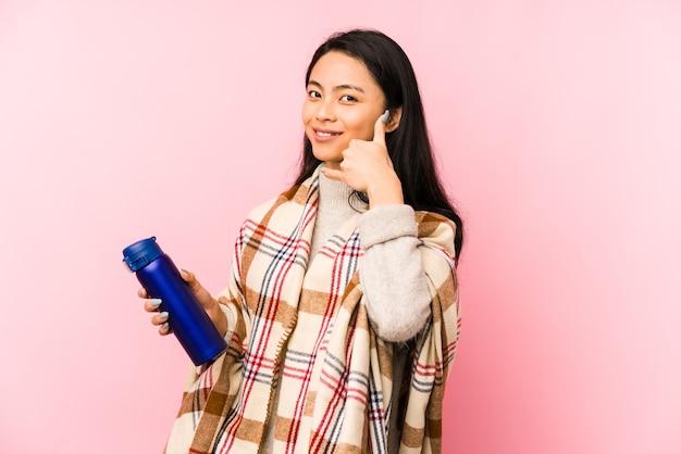 Giovane donna cinese che fa un campeggio isolato sul rosa che riceve una piacevole sorpresa, eccitata e alzando le mani.