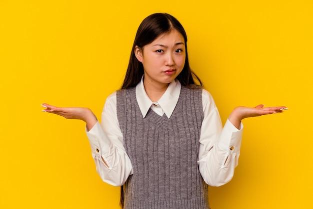 Giovane donna cinese che dubita e scrolla le spalle le spalle nel gesto interrogativo.