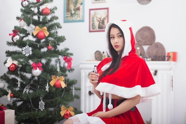 Giovane donna cinese vestita da babbo natale che tiene sigaretta elettronica vicino all'albero di natale
