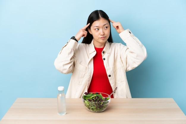 Giovane donna cinese che mangia un'insalata che ha dubbi e pensiero