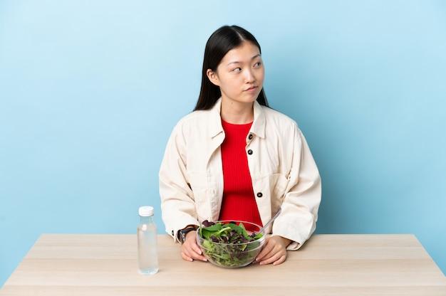 Giovane donna cinese che mangia un'insalata che ha dubbi mentre osservando lato