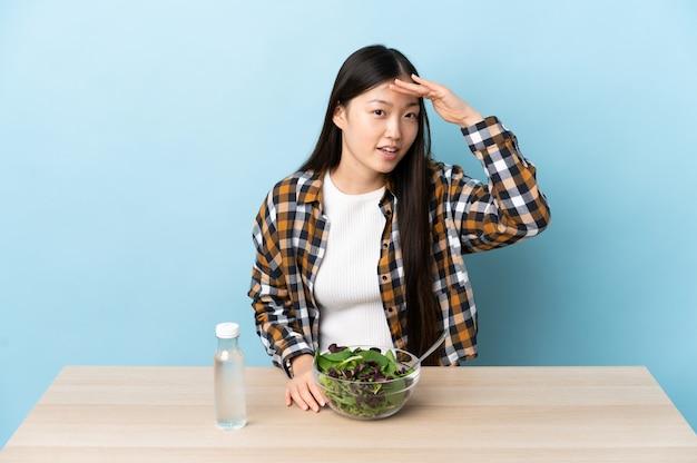 Giovane donna cinese che mangia un'insalata che guarda lontano con la mano per guardare qualcosa