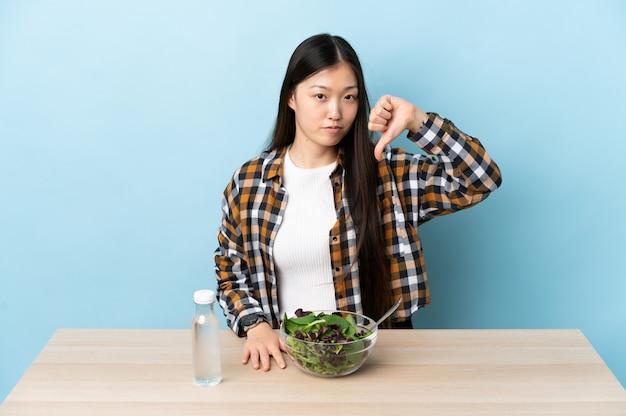 Giovane donna cinese che mangia un'insalata che mostra pollice giù con l'espressione negativa