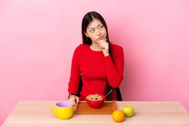 Giovane donna cinese che mangia prima colazione in una tabella che ha dubbi