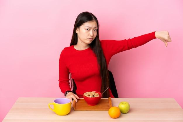 Giovane donna cinese che mangia prima colazione in una tabella che mostra pollice giù con l'espressione negativa