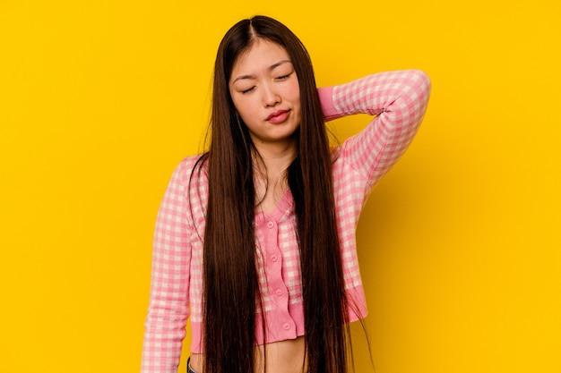 Giovane donna cinese che ha un dolore al collo a causa dello stress, massaggiandolo e toccandolo con la mano.