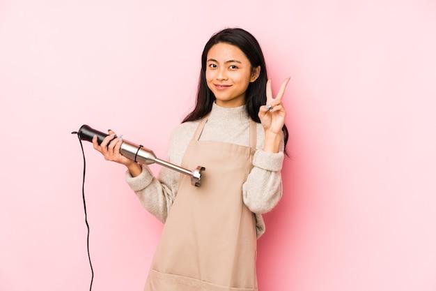 Giovane donna cinese che tiene un mixer isolato con le dita sulle labbra mantenendo un segreto.