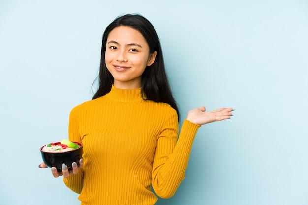 La giovane donna cinese che tiene le tagliatelle ha isolato il pensiero rilassato a qualcosa che esamina uno spazio della copia.
