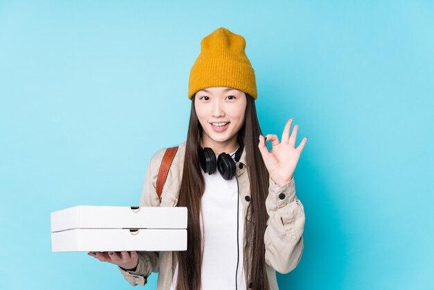 La giovane donna cinese che tiene le pizze ha isolato allegro e sicuro che mostra gesto giusto.