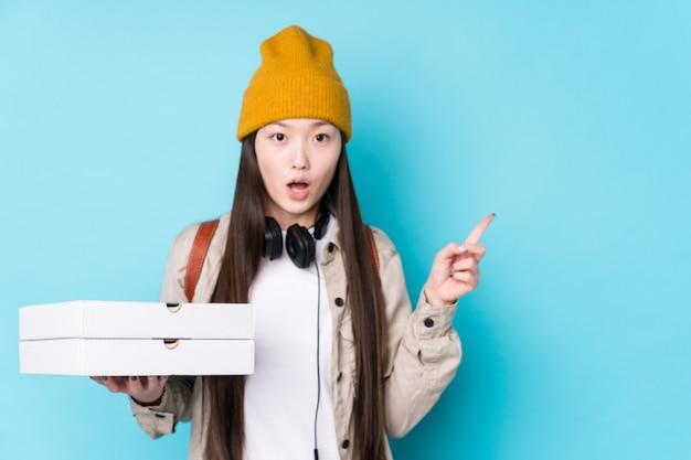 Pizze cinesi della holding della giovane donna isolate che indicano il lato