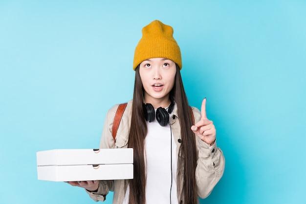 La giovane donna cinese che tiene le pizze ha isolato la parte superiore rivolta con la bocca aperta.
