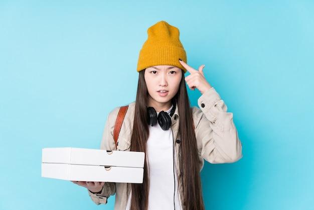 Pizze cinesi della holding della giovane donna isolate che mostrano un gesto di delusione con l'indice.