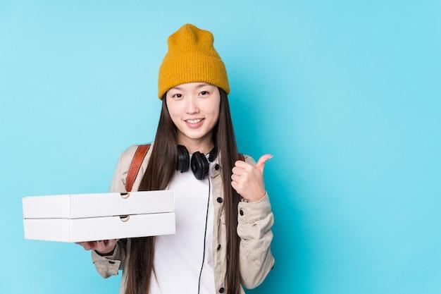 La giovane donna cinese che tiene le pizze isolate sorridendo e alzando il pollice in su