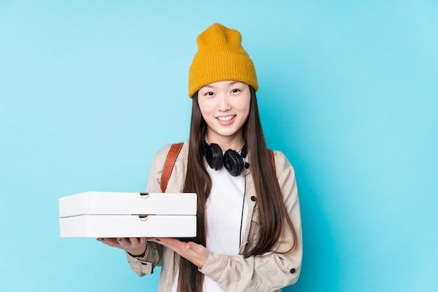 Giovane donna cinese tenendo le pizze ridendo e divertendosi.