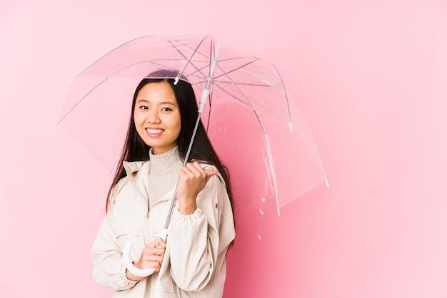 La giovane donna cinese che tiene un ombrello ha isolato i punti con il dito del pollice via, ridendo e spensierato.