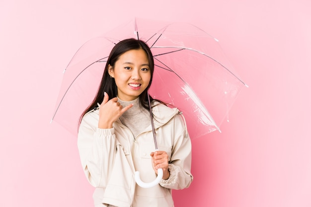 Giovane donna cinese che tiene un ombrello isolato che mostra un gesto di chiamata di telefono cellulare con le dita.