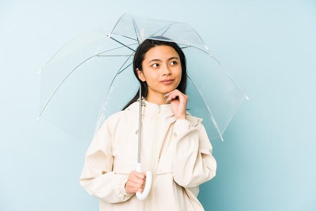 Giovane donna cinese che tiene un ombrello isolato che mostra il numero uno con il dito.