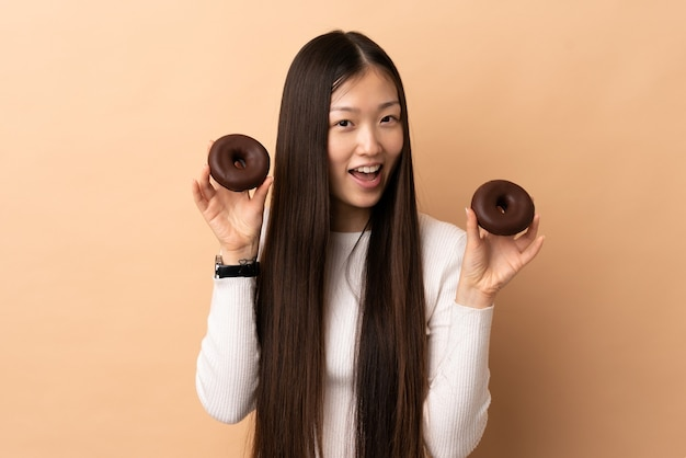 Giovane donna cinese su ciambelle azienda isolata con felice espressione