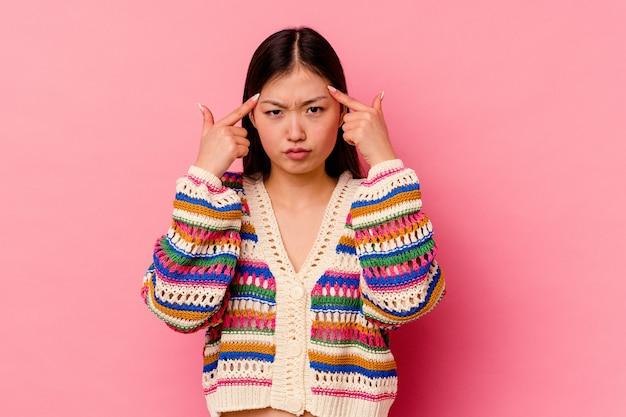 La giovane donna cinese isolata su fondo rosa si è concentrata su un compito, mantenendo gli indici che puntano la testa.